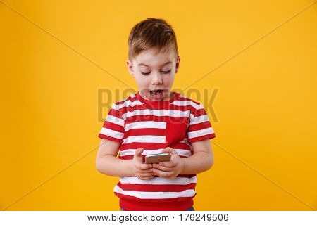 Portrait of a clever excited little boy reading message on mobile phone isolated over orange background