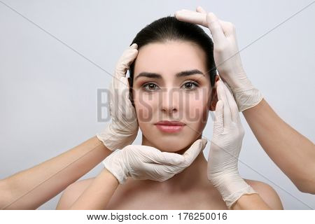 Hands in rubber gloves touching face of young beautiful woman, on light background