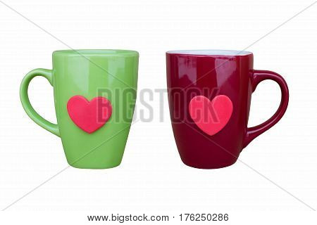 Green ceramic mug and maroon ceramic mug decorated with red heart on white background close-up