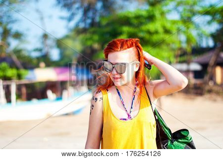 Beautiful young girl with shaved temples and red hair with a tattoo and wearing sunglasses.