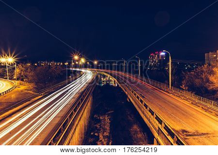 Bridge, curve road, night city landscape, freezelight car lights, long exposure, view from above. Night city traffic concept. Voronezh, Dinamo. Toned image