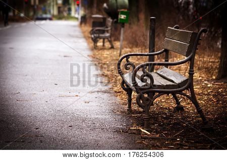 Poland, Szczecin. Original old wooden bench in the city park in the autumn cloudy day