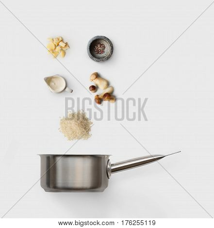 Cooking italian food, risotto with wild mushrooms, isolated on white background. Rice, fungus, sauce, parmesan and other ingredients over saucepan
