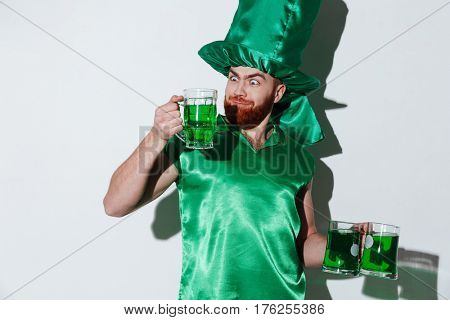Funny bearded man in green costume which holding cups of green beer over gray background