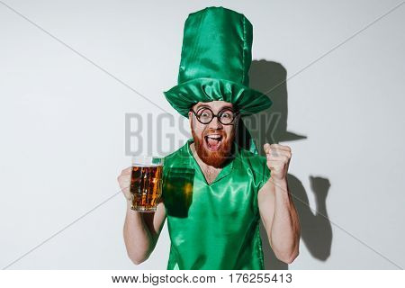 Portrait of screaming man in st.patriks costume and eyeglasses which holding cup of beer and looking at camera. Isolated gray background
