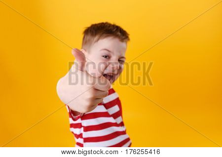 Portrait of a smiling active little boy showing thumbs up isolated over orange background, focus camera on a fist