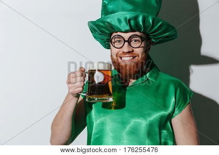 Smiling guy in st.patriks costume and eyeglasses which holding cup of beer and looking at camera over gray background