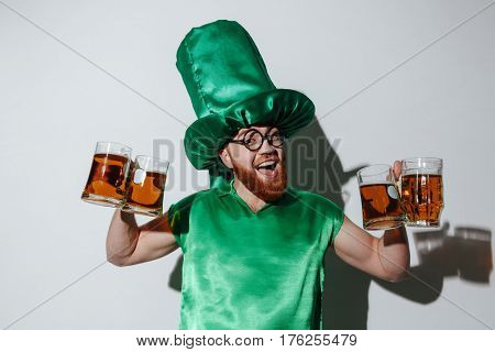 Bearded guy in st.patriks costume and eyeglasses which holding many cups and looking at camera. Isolated gray background