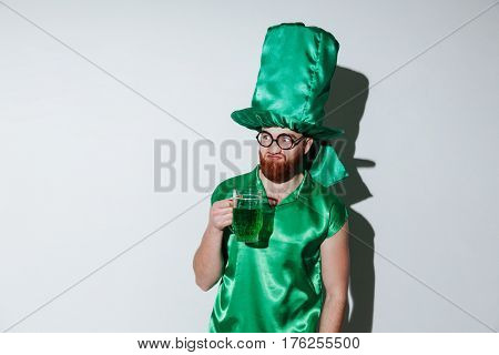 Bearded man in green costume of st.patriks and eyeglasses which holding cup of green beer over gray background