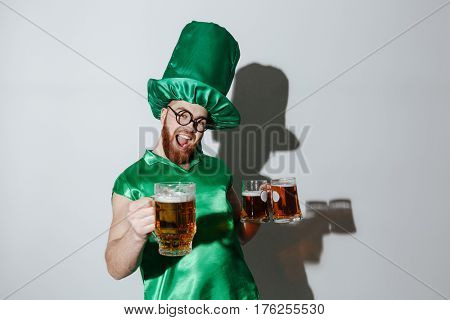 Screaming happy man in st.patriks costume and eyeglasses which holding cups of beer and looking at camera. Isolated gray background