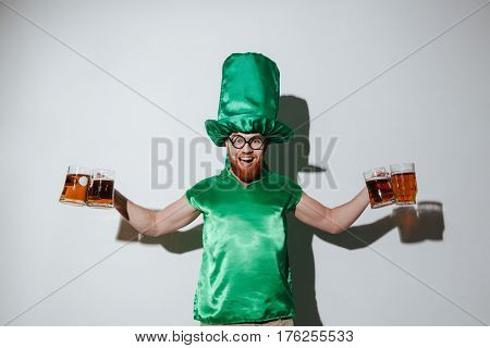 Smiling guy in st.patriks costume and eyeglasses which holding many cups of beer and looking at camera over gray background
