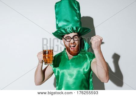 Happy man in st.patriks costume and eyeglasses which holding cup of beer and looking at camera. Isolated gray background