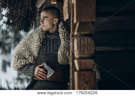 Ancient Viking Warrior With Steel Axe Posing Near Wooden Hut In Scandinavian Winter Forest, Thor Vik