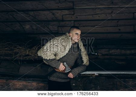 Strong angry viking warrior with axe before battle at war ancient scandinavian warrior cosplay thor costume northern lumberjack costume confident facial expression of man near wooden building poster