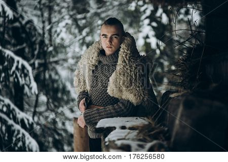 Viking Warrior With Steel Axe Posing Near Wooden Hut In Scandinavian Winter Forest, Thor Viking Cosp