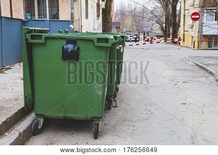 Old green dumpsters on the street. Household waste in the city.