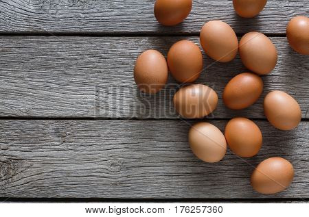 Fresh chicken brown and white home eggs on rustic wood table. Top view with copy space. Rural still life, natural healthy food and organic farming concept.