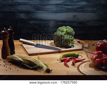 Fresh broccoli on wooden board with knife. Low key shot, light on board, some vegetables around on table. Copy space.