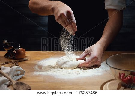 Cook hands kneading dough, sprinkling piece of dough with white wheat flour. Low key shot; close up on hands; some ingredients around on table.