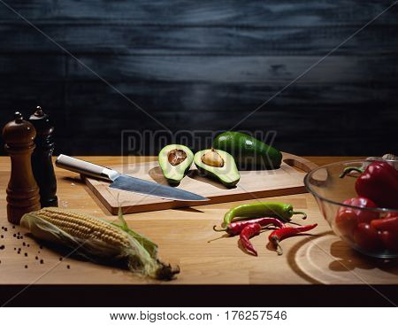 Halved and whole ripe avocados on wooden board with knife. Low key shot; light on board; some vegetables around on table. Copy space.