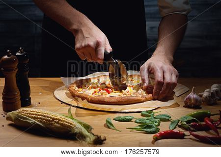 Chef cutting freshly baked hawaiian pizza. Low key shot, close up of hands, some ingredients around on table.