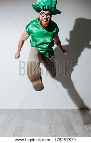 Vertical image of happy man in st.patriks costume and eyeglasses which jumping in studio. Isolated gray background