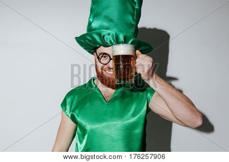Pleased man in st.patriks costume and eyeglasses which holding cup of beer near the face and looking at camera. Isolated gray background