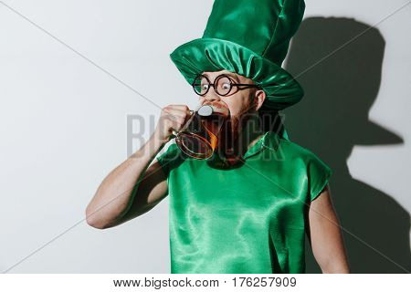 Funny drunk man in st.patriks costume and eyeglasses which drinking beer in studio over gray background