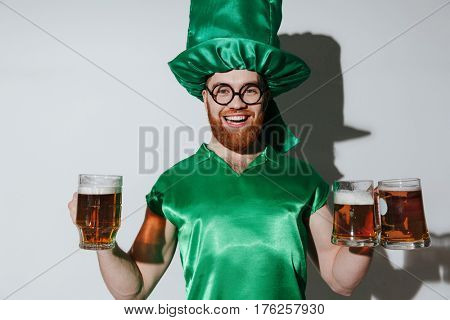 Happy man in st.patriks costume and eyeglasses which holding cups of beer and looking at camera over gray background