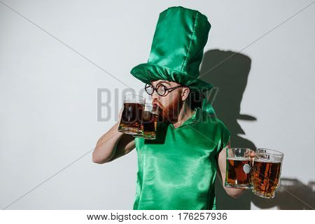 Funny man in st.patriks costume and eyeglasses which drinking beer from two cups while holding two more cups of beer over gray background