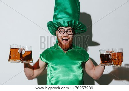Happy guy in st.patriks costume and eyeglasses which holding many cups of beer and looking at camera. Isolated gray background