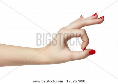 Woman hand in ok sign with manicure and red nails on a white isolated background