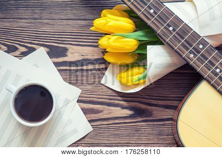 Beautiful spring background music. Guitar yellow tulips cup of coffee musical page on a dark wooden background. Shallow depth of field. Coloring photo with soft focus in instagram style.