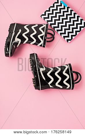 The Black and white rubber boots or gardening boots on pink studio background
