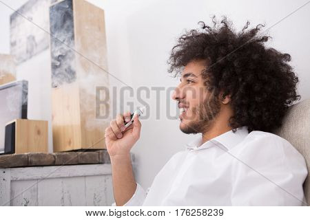 Handsome man having break while working at home alone. Hipster man enjoys e-cigarette so much while having free time during work.
