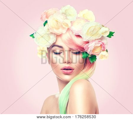 Spring Woman. Beauty Summer model girl with colorful flowers wreath and colorful hair. Flowers Hair Style. Beautiful Lady with Blooming flowers on her head. Nature Hairstyle. Holiday Fashion Makeup