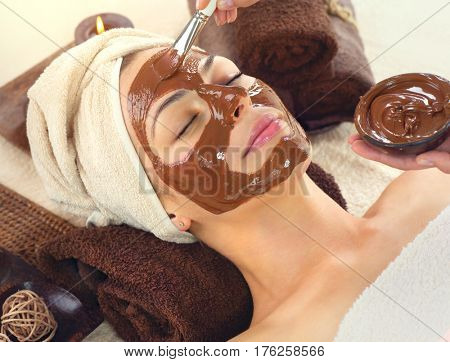 Chocolate Luxury Spa. Facial Mask. Beautiful young woman relaxing in beauty spa salon, applying chocolate face mask