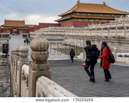 Beijing, China - Oct 30, 2016: Visitors at the Forbidden City (Gu Gong, Palace Museum). The Hall of Supreme Harmony (Taihedian) sits elevated on tiered terraces (right of image). Exit side gate to the left.