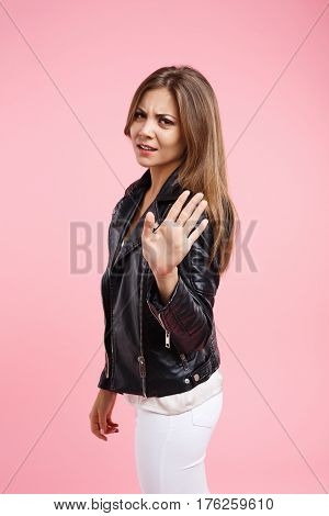 Irritated and tired woman shows stop sign with hand looking straight at camera with anger
