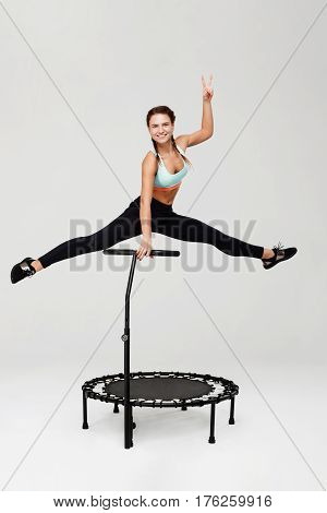 Young sporty woman doing split jumping up showing peace sign smiling cheerfully looking straight