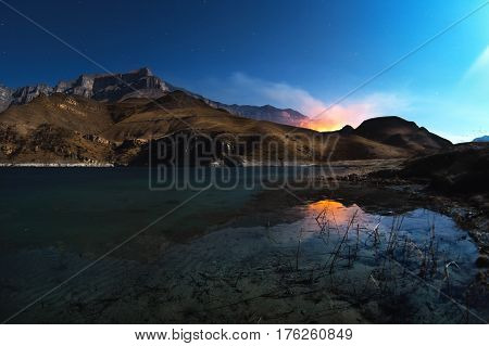 A beautiful night landscape with a reflection of rocks in a mountain lake, in the moonlight with the burning mountains in the background