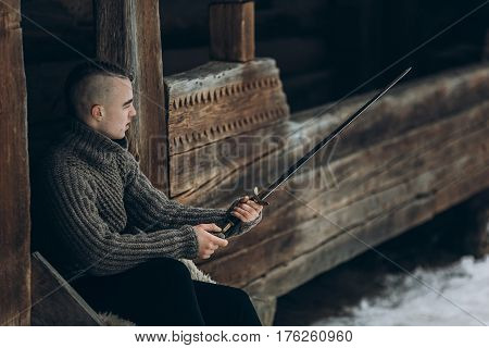Brave Warrior Holding Sword Near Historical Wood Castle Building In Winter Woods In Scandinavia, Han