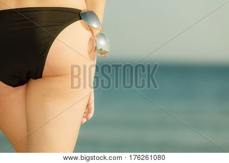 Summertime underwear being confident during summer concept. Woman bottom bum in black bikini panties and glasses. Sea background.