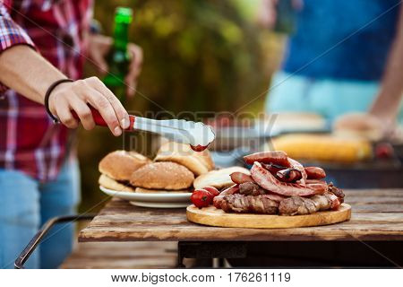 Young handsome men roasting barbecue on grill in cottage countryside. Copy space.