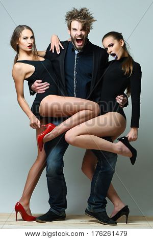 Two pretty girls or sexy fit women in sexi bodysuits with black and red high heel shoes on slim legs hugging bearded shouting man caucasian hipster with beard stylish haircut on grey background