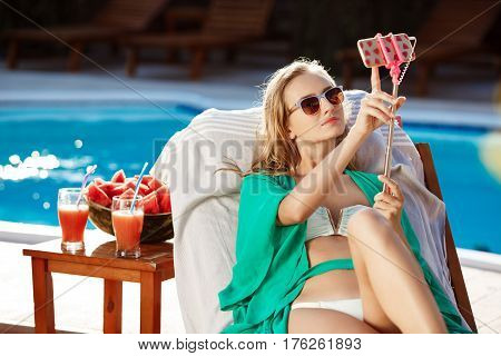 Beautiful blonde girl smiling, making selfie, lying on chaise near swimming pool. Copy space.