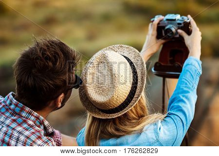 Young beautiful couple of travelers making selfie on old camera, canyon background. Copy space.