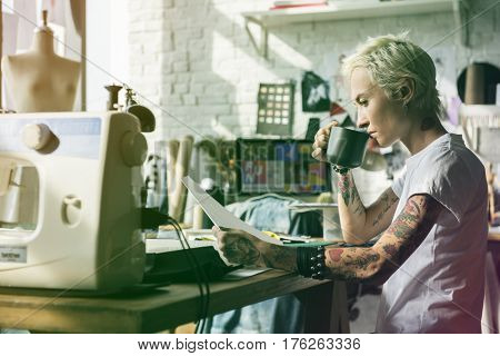 Fashion designer tattooed girl drinking and looking at sketch