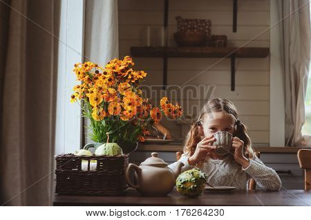 child girl having breakfast at home in autumn morning. Real life cozy modern interior in country house. Kid eating bagels and drinking tea.