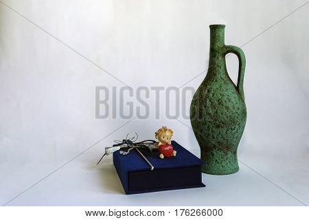On a white background are arranged: a jug for wine and a blue box for gifts with silver braid and a bow. She has an angel figure with a red heart in her hands and an inscription